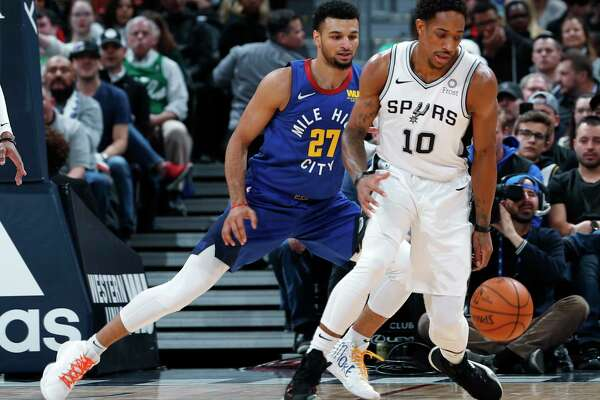 San Antonio Spurs guard Patty Mills, left, passes the ball as Denver Nuggets guard Jamal Murray defends during the first half of an NBA basketball game Friday, Feb. 23, 2018, in Denver. (AP Photo/David Zalubowski)