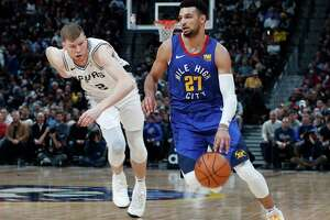 San Antonio Spurs forward LaMarcus Aldridge, left, fights for control of a loose ball with Denver Nuggets forward Wilson Chandler during the first half of an NBA basketball game Friday, Feb. 23, 2018, in Denver. (AP Photo/David Zalubowski)