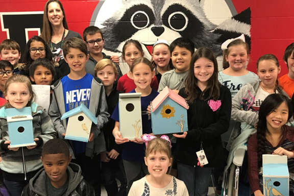 Fourth-graders at Woodland Hills Elementary School hold the birdhouses they designed for a math project.
