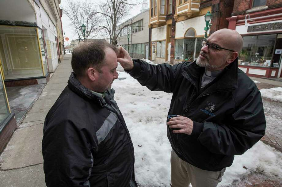 Pastor Deron Millville, right, lays ashes on the forehead of a person as they take part in the Ashes To Go program on the Jay Street pedestrian walkway Wednesday Feb. 14, 2018 in Schenectady, N.Y. (Skip Dickstein/Times Union) Photo: SKIP DICKSTEIN, Albany Times Union / 20042917A
