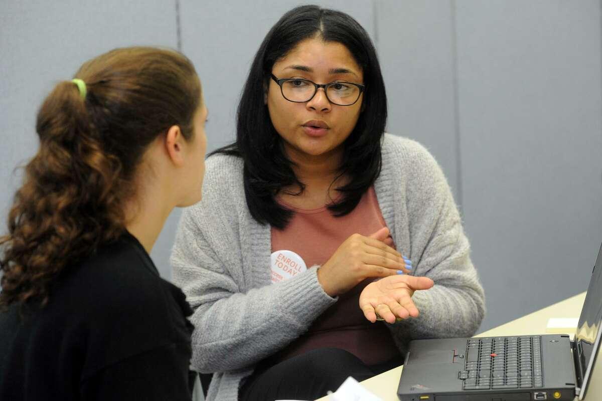 Access Health CT enrollment specialist Gabriela Tejada, right, helps a customer in early November 2017 in Bridgeport, Conn.