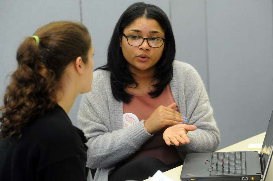 Access Health CT enrollment specialist Gabriela Tejada, right, helps a customer in early November 2017 in Bridgeport, Conn. Photo: Ned Gerard / Hearst Connecticut Media / Connecticut Post
