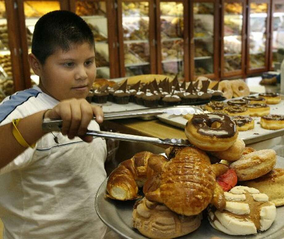 Juan Jose Cano Meza loads up on a variety of Mexican baked goods as he purchases bread at El Bolillo Panaderia, a popular Mexican bakery near the produce market on Airline. Photo: Carlos Antonio Rios, Houston Chronicle