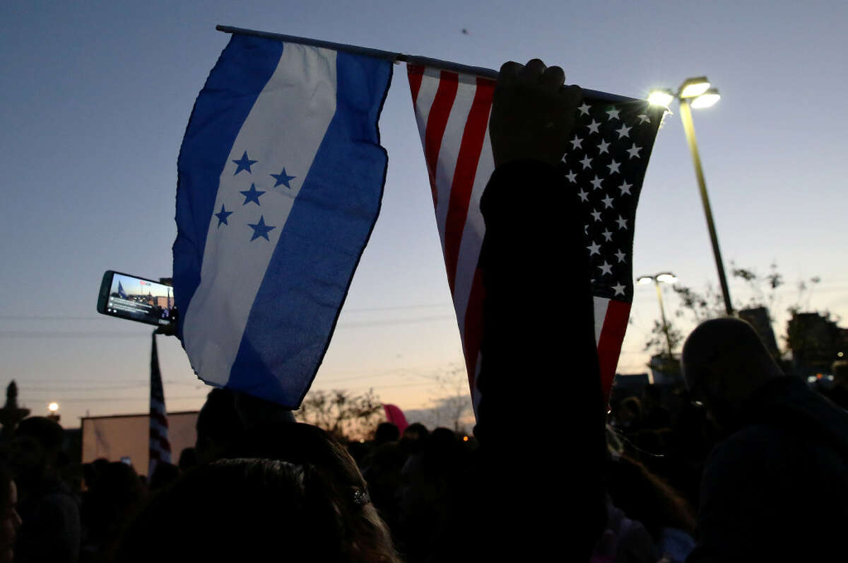 """Marina Rodriguez raises a Honduras flag and an American flag to represent her identification during the """"Day Without Immigrants"""" protest at Guadalupe Plaza Thursday, Feb. 16, 2017, in Houston. ( Yi-Chin Lee / Houston Chronicle )"""