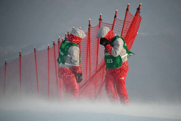 Stewards adjust a net as winds blow after the Alpine Skiing Women's Slalom was cancelled due to weather conditions at the Jeongseon Alpine Center during the Pyeongchang 2018 Winter Olympic Games in Pyeongchang on February 14, 2018. Photo: FABRICE COFFRINI/AFP/Getty Images