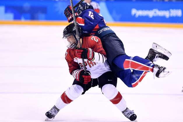 Japan's Shoko Ono and Unified Korea's Kim Heewon (R) collide in the women's preliminary round ice hockey match between Japan and the Unified Korean team during the Pyeongchang 2018 Winter Olympic Games at the Kwandong Hockey Centre in Gangneung on February 14, 2018. Photo: BRENDAN SMIALOWSKI/AFP/Getty Images