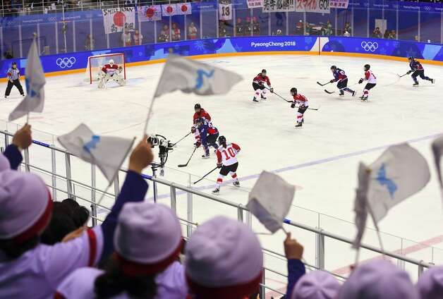 North Korean cheerleaders wave the Korean unification flags and cheer during the women's preliminary round ice hockey match between Japan and the Unified Korean team during the Pyeongchang 2018 Winter Olympic Games at the Kwandong Hockey Centre in Gangneung on February 14, 2018. Photo: JUNG YEON-JE/AFP/Getty Images