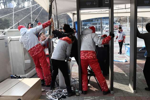 Volunteers try to stop a security control tent from flying away by strong winds outside the Gangneung Ice Arena in Gangneung during the Pyeongchang 2018 Winter Olympic Games on February 14, 2018. Photo: ARIS MESSINIS/AFP/Getty Images