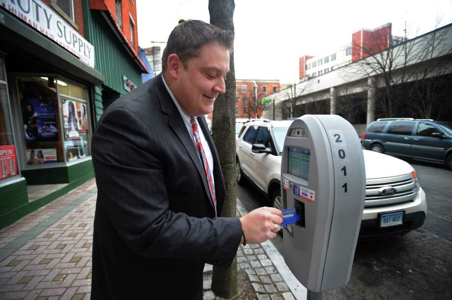 Bridgeport attorney Peter Karayiannis pays at a parking meter on Wall Street before heading in to court in Bridgeport, Conn. on Wednesday, February 14, 2018. Photo: Brian A. Pounds, Hearst Connecticut Media / Connecticut Post