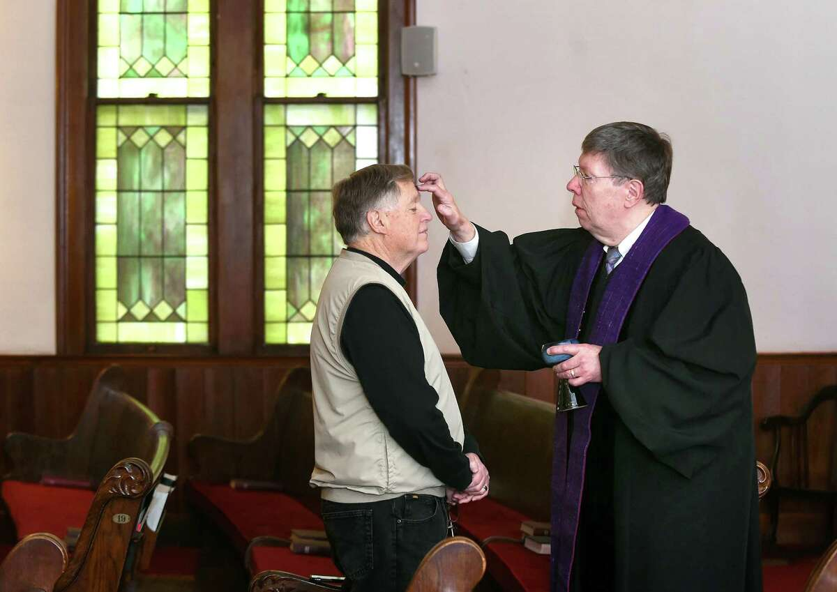 Terry Parsons of Guilford receives ashes from Rev. Vance Taylor at North Branford Congregational Church during the Ash on Your Dash! event for Ash Wednesday on February 14, 2018.