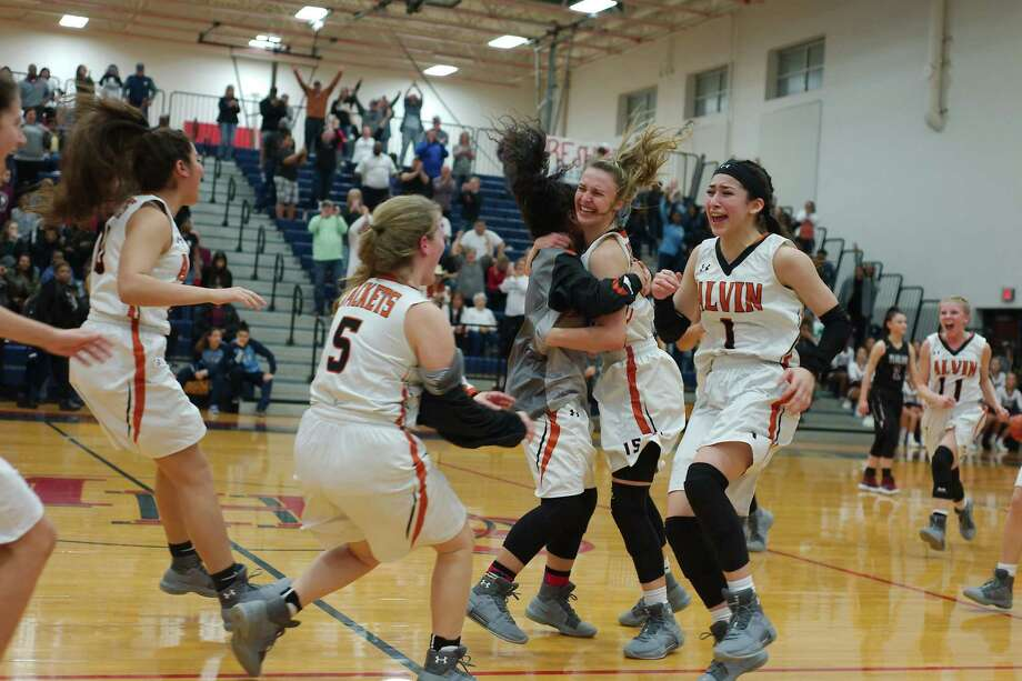 Alvin players, among them Andreea Mancha (1) and Kayla Palmer (5),  celebrate their 49-42 win over Pearland Monday night in a Class 6A girls' bi-district playoff game in Manvel. Photo: Kirk Sides
