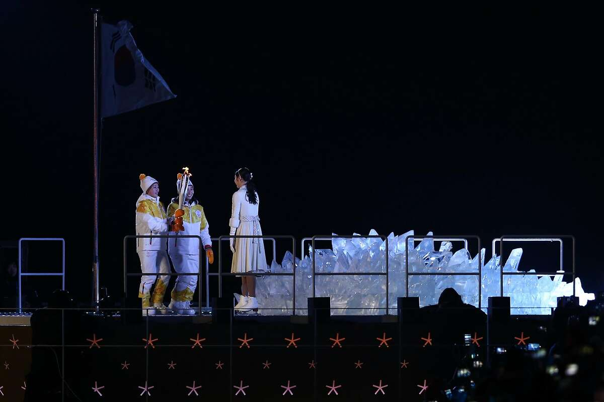 PYEONGCHANG-GUN, SOUTH KOREA - FEBRUARY 09: Hockey players Chung Su-hyon of North Korea and Park Jong-ah of South Korea hand the Olympic torch to South Korean figure skater Yuna Kim to lit the Cauldron during the Opening Ceremony of the PyeongChang 2018 Winter Olympic Games at PyeongChang Olympic Stadium on February 9, 2018 in Pyeongchang-gun, South Korea. (Photo by Dan Istitene/Getty Images)