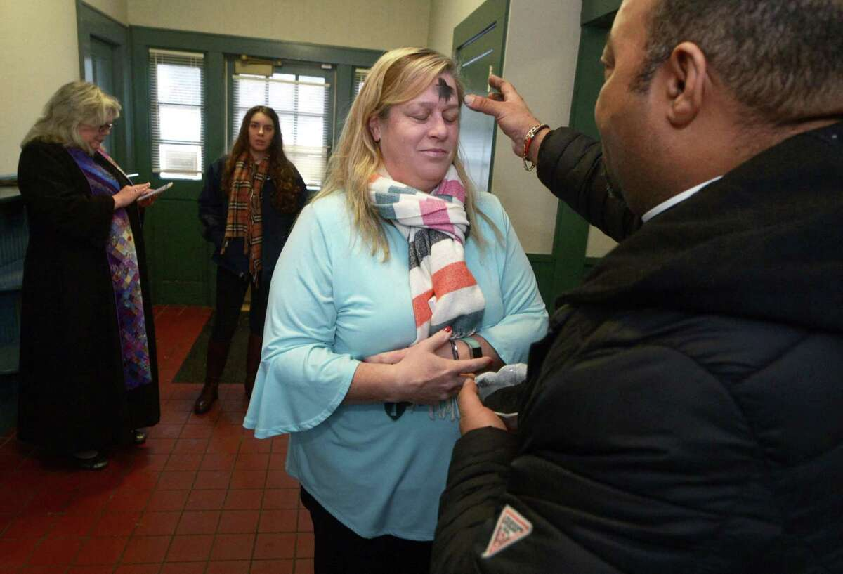 Father Reggie Norman of Our Lady of Fatima Parish distributes ashes to Mary Rooney of Norwalk Wednesday the Wilton Train Station. Commuters and other people on-the-go have stopped by for ashes since Father Norman started distributing ashes at the train station in 2013.