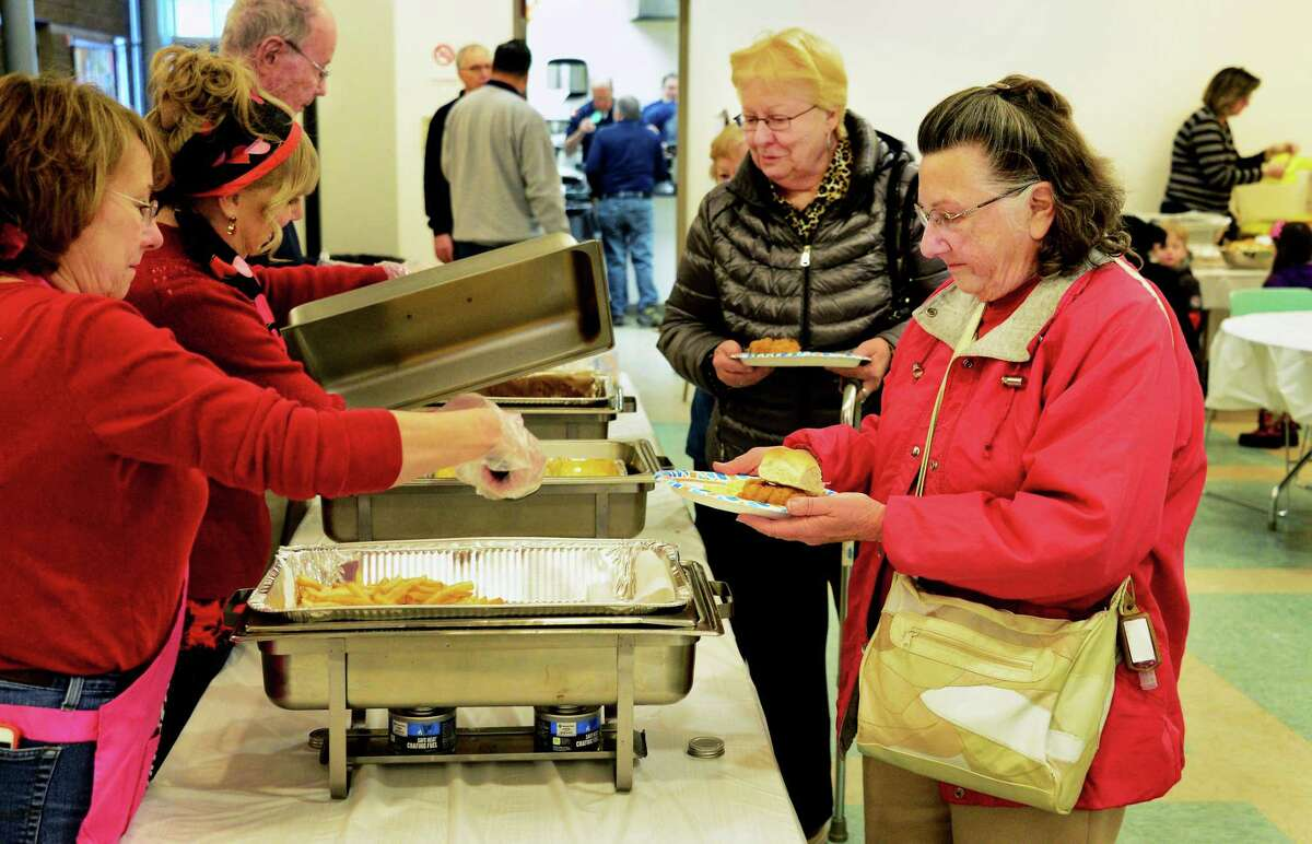 Rose Grady, center, of Clifton Park and Theresa Baum of Johnsonvill, right, are served a Fish Fry Dinner during St. Edward's Church's annual Ash Wednesday Fish Fry Dinner Feb. 14, 2018 in Clifton Park, NY. (John Carl D'Annibale/Times Union)