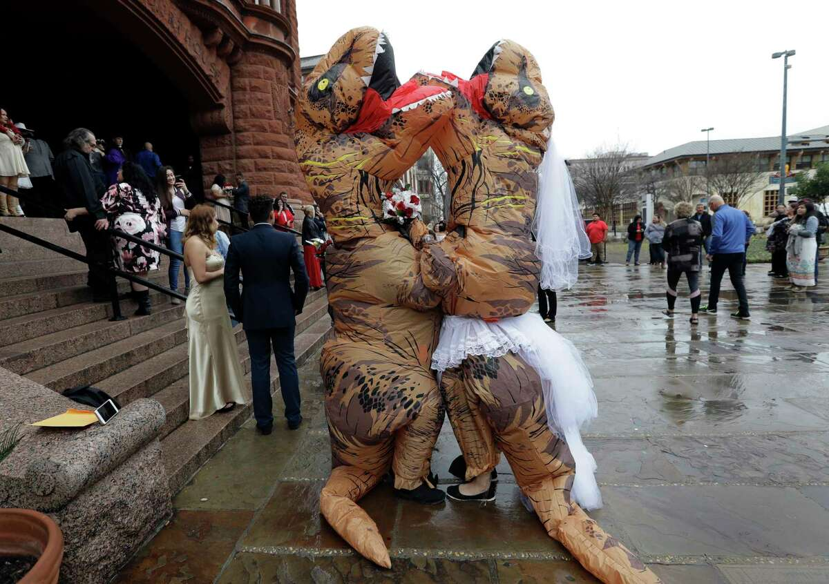 Brian and Tanya Hankinson, dressed in dinosaur costumes, wait at the steps the Bexar County Courthouse for a mass wedding to begin, Wednesday, Feb. 14, 2018, in San Antonio. The couple took part in a Valentine's Day mass wedding of more than 40 couples at the courthouse. (AP Photo/Eric Gay)