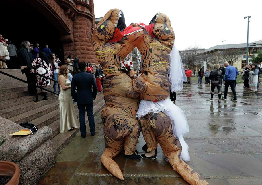 Brian and Tanya Hankinson, dressed in dinosaur costumes, wait at the steps the Bexar County Courthouse for a mass wedding to begin, Wednesday, Feb. 14, 2018, in San Antonio. The couple took part in a Valentine's Day mass wedding of more than 40 couples at the courthouse. (AP Photo/Eric Gay) Photo: Eric Gay, Associated Press / Copyright 2018 The Associated Press. All rights reserved.
