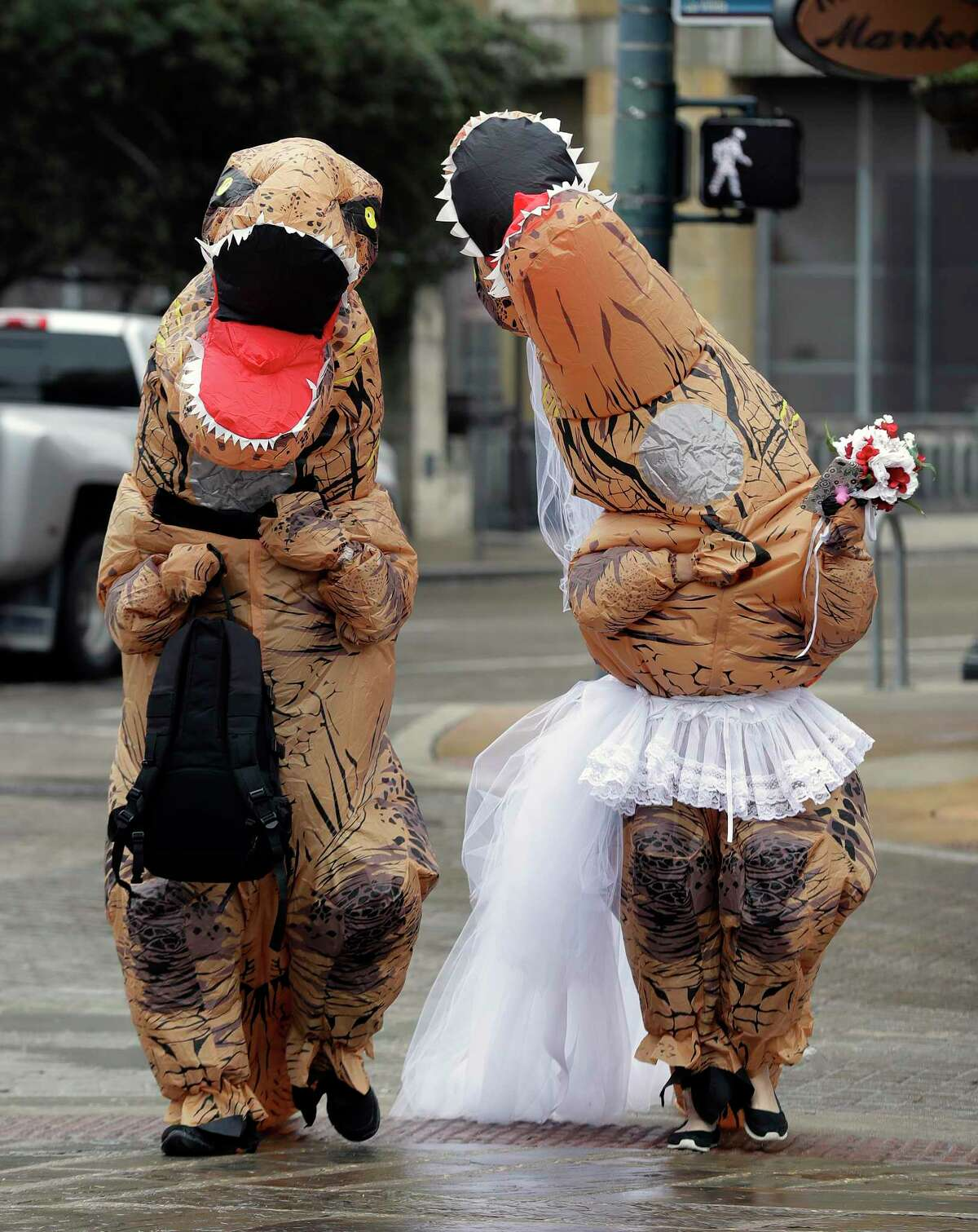 Brian and Tanya Hankinson arrive at the Bexar County Courthouse dressed in dinosaur costumes, Wednesday, Feb. 14, 2018, in San Antonio. The couple took part in a Valentine's Day mass wedding of more than 40 couples at the courthouse. (AP Photo/Eric Gay)