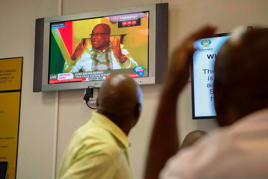 South Africans watch a TV broadcast of President Jacob Zuma in Cape Town. Lawmakers in Parliament could topple Zuma by voting on a motion of no confidence Thursday. Photo: RODGER BOSCH, AFP/Getty Images