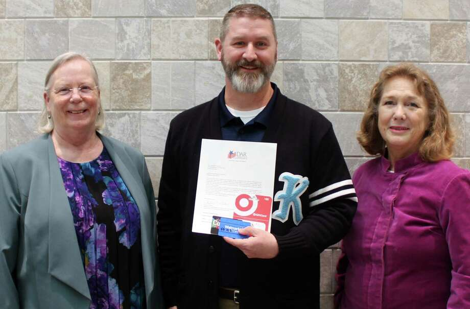Ella Guaqueta (left) and Linda Abdmoulaie (right) with Daughters of the American Revolution's Lady Houston Chapter, pose for a photo with Kingwood High School principal Ted Landry (center) after presenting him with $750 in Target and Walmart gift cards on Monday, Feb. 12 at Summer Creek High School. Photo: Melanie Feuk