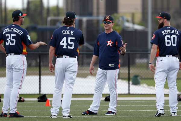 Houston Astros pitchers Justin Verlander (35), Gerrit Cole (45), and Dallas Keuchel (60) talk with manager A.J. Hinch during warmups as the pitchers and catchers worked out for the first time during spring training at The Ballpark of the Palm Beaches, Wednesday, Feb. 14, 2018, in West Palm Beach .