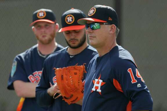 Houston Astros manager A.J. Hinch listens as pitching coach Brent Strom meets with pitchers as they worked out for the first time during spring training at The Ballpark of the Palm Beaches, Wednesday, Feb. 14, 2018, in West Palm Beach .