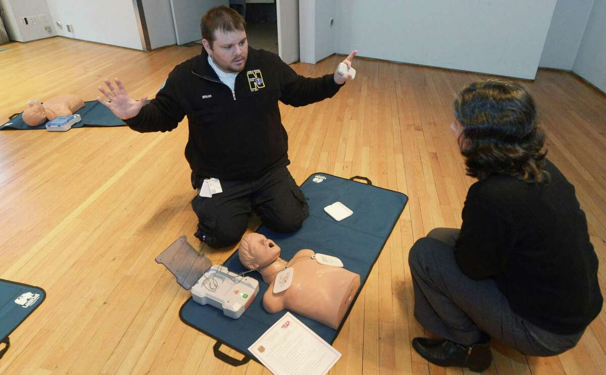 Norwalk EMT Brian Hepp instructs Norwalk Corporation Council Legal Assistant Irene Alarcon as the Norwalk Fire Department and Norwalk Hospital EMS provide free Hands Only CPR training in City Hall. In less than 15 minutes, residents learned the basic skills needed to save the life of a loved one or friend.