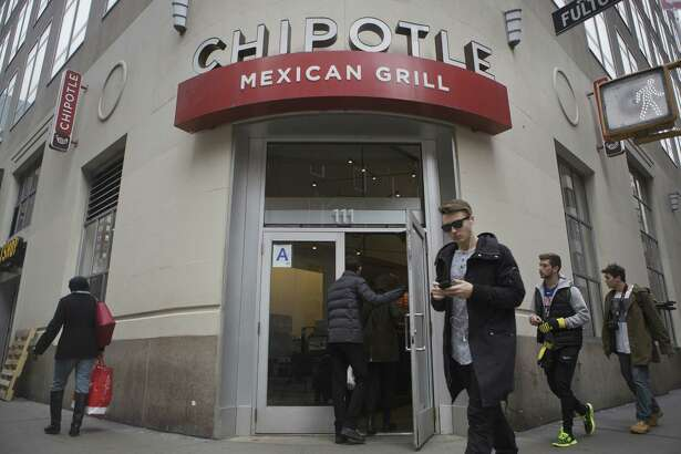 Pedestrians pass a Chipotle Mexican Grill restaurant in New York on Jan. 29, 2016. (