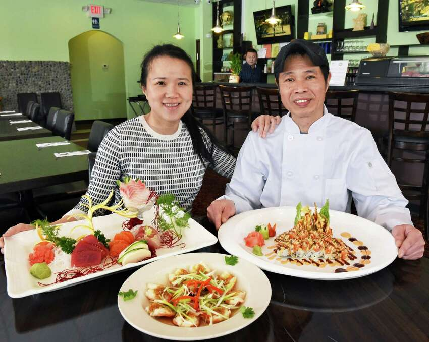 Jessica and Kevin Hsu with dishes of, from left, Sashimi Deluxe, steamed shrimp with fresh garlic and Out of Control, a full soft-shell crab and spicy tuna with vegetables, in their Pebbles Asian Fusion restaurant Saturday Feb. 10, 2018 in Colonie, NY. (John Carl D'Annibale/Times Union)