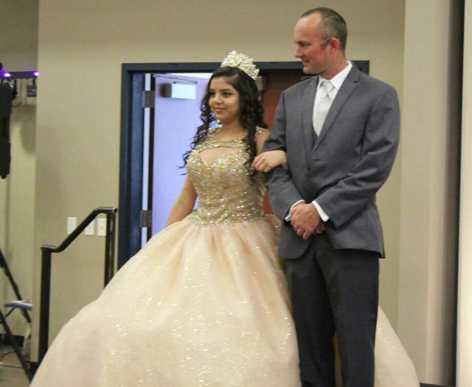 Crystal Aguilera (left) showcases a dress for quinceaneras on Feb. 10 while being escorted by David Everhart (right) at the Glamour Expo in Cleveland. Photo: Jacob McAdams
