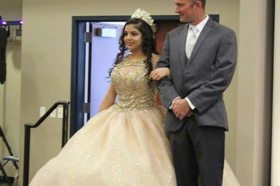 Crystal Aguilera (left) showcases a dress for quinceaneras on Feb. 10 while being escorted by David Everhart (right) at the Glamour Expo in Cleveland.