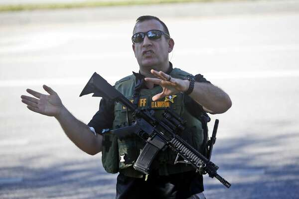 A law enforcement officer tells anxious family members to move back, Wednesday, Feb. 14, 2018, in Parkland, Fla. A shooting at Marjory Stoneman Douglas High School sent students rushing into the streets as SWAT team members swarmed in and locked down the building. Police were warning that the shooter was still at large even as ambulances converged on the scene and emergency workers appeared to be treating those possibly wounded. (AP Photo/Wilfredo Lee)