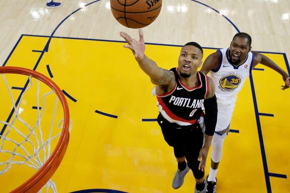 Damian Lillard (0) puts up a shot during the first half as the Golden State Warriors played the Portland Trail Blazers at Oracle Arena in Oakland, Calif., on Monday, December 11, 2017.