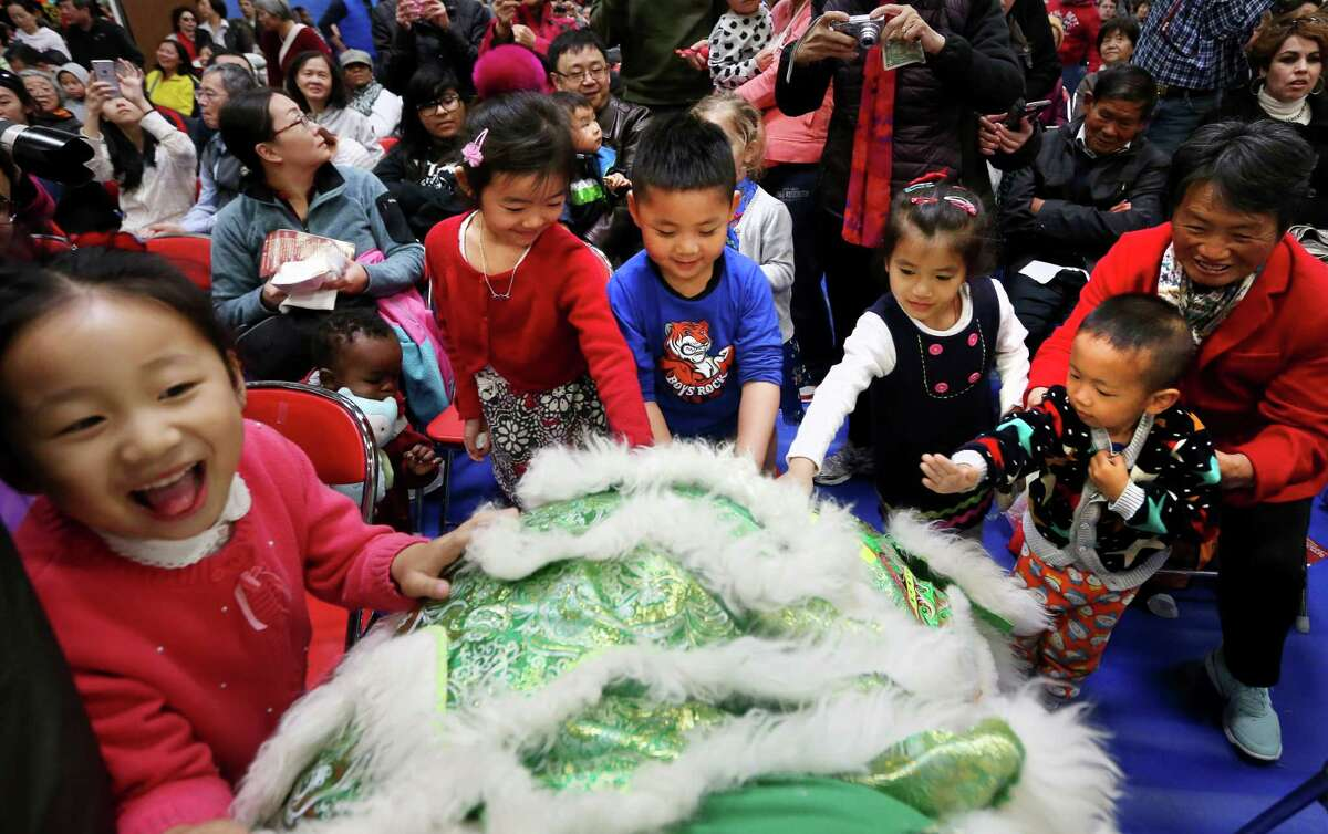 Children greet a lion during a lion dance performed by Lavang Lion Dance Team at the Lunar New Year Festival at the Chinese Community Center Saturday, Feb. 6, 2016, in Houston. ( Jon Shapley / Houston Chronicle )
