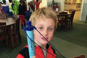 Teddy Kowalchick, third grader at Rumsey Hall School, holds up a LifeStraw, which filters unclean water to make it drinkable. Students raised enough to send three community LifeStraws to a school in Puerto Rico affected by the hurricane.