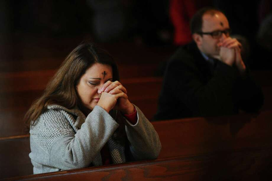 Congregants pray after receiving ashes for Ash Wednesday inside the Church of the Holy Spirit on Scofieldtown Road in Stamford, Conn. on Wednesday, Feb. 14, 2018. Photo: Michael Cummo / Hearst Connecticut Media / Stamford Advocate