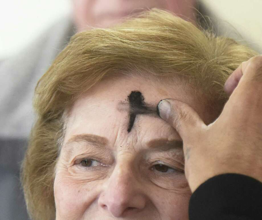 Joyce Mirizio receives ashes for Ash Wednesday at the Stamford Lincoln Ford dealership in Stamford, Conn. Wednesday, Feb. 14, 2018. Christians celebrated Ash Wednesday to mark the start of Lent, which is six weeks of repentance before Easter. Photo: Tyler Sizemore / Hearst Connecticut Media / Greenwich Time