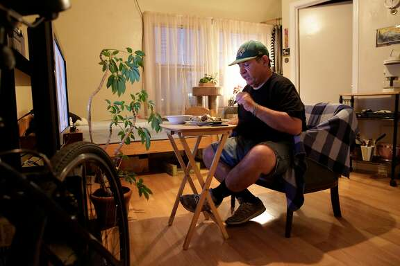 Steve Summers sits down to enjoy his evening meal in his apartment in  Oakland, Calif., seen on Tuesday Feb. 13, 2018. Summers relies on the benefits of the Federal governments Supplemental Nutritional Assistance Program, (food stamps) to buy the fresh pork to make salsa verde with brussels sprout as well as items like rice from a local food pantry.