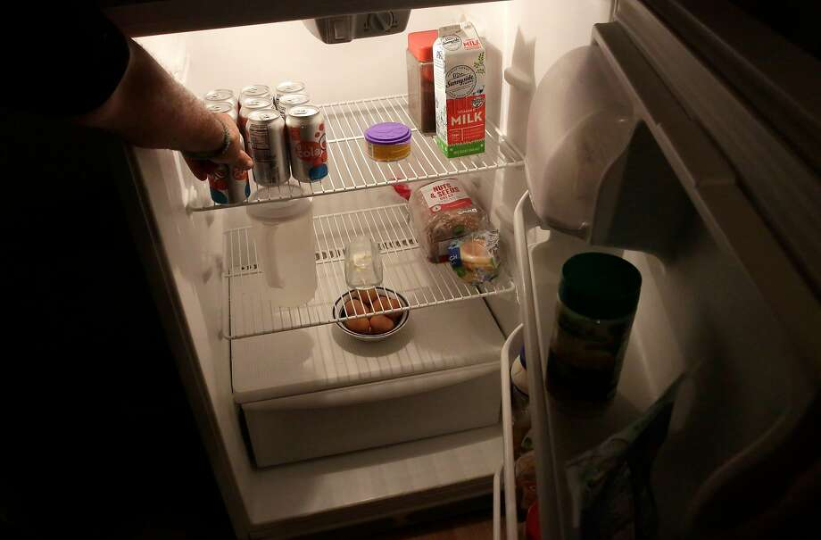 Summers reaches into his sparsely stocked refrigerator to take out items. The proposed meal kit would contain mainly canned foods. Photo: Michael Macor, The Chronicle