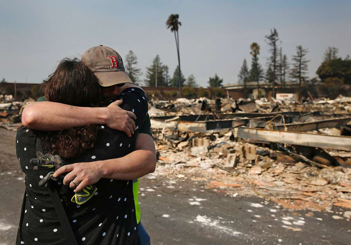 Family members embrace at a destroyed home containing the remains, they believe, of their family member at Journey's End mobile home park Oct. 11, 2017 in Santa Rosa, Calif. Most of the mobile homes were destroyed in the blaze, except for the last row of homes, reportedly because a resident named Priest stayed behind and fought the blaze with a hose the fire department gave him.