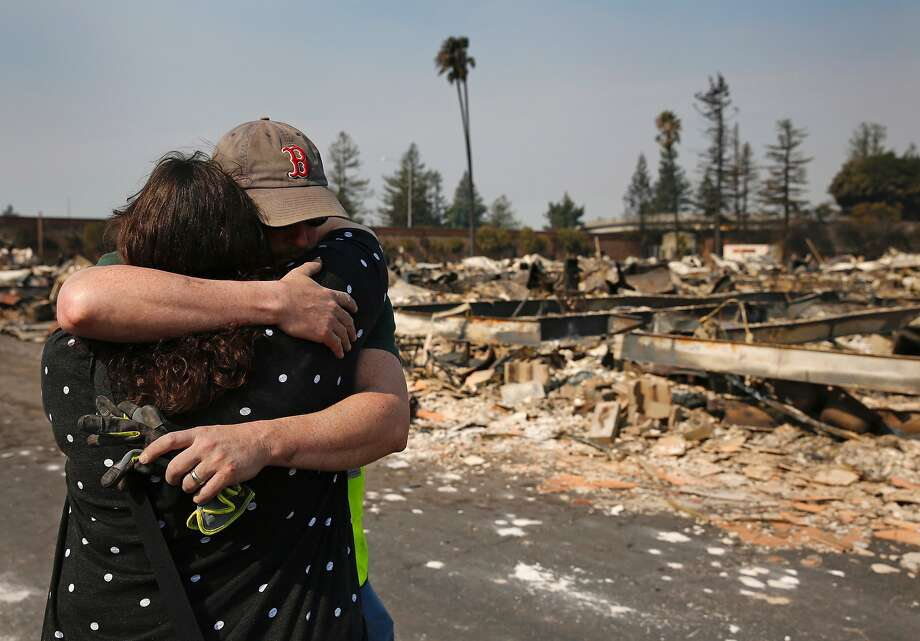 Family members embrace at a destroyed home at Journey's End mobile home park on Oct. 11, 2017 in Santa Rosa. Photo: Leah Millis, The Chronicle