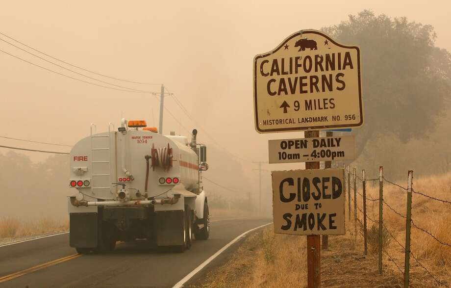 A water truck passes a warning sign that the California Caverns historic site in Calaveras County is closed due to smoke from the Butte Fire, on Sept. 12, 2015. Calaveras County supervisors voted unanimously Tuesday to sue Pacific Gas and Electric Co. over the deadly fire. Photo: Rich Pedroncelli, Associated Press
