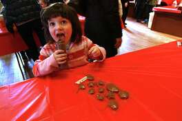 Emily Murphy, 4, of Monroe, licks the bottle of chocolate she used to make her own Valentine Day candies during the Kids' Candymaking Workshop held at the Pequot Library in Southport, Conn., on Tuesday Feb. 13, 2018. The kids from kindergarten to 8th grade were able to make chocolate treats for Valentine's Day. They were also able to use crafts to create their own gift box and card. For future events or information, visit: www.pequotlibrary.org