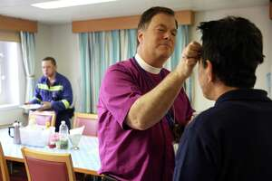 Bishop Greg Rickle blesses a crew member of the APL Southhampton with ashes on Ash Wednesday, Feb. 14, 2018. Rickle and other members of the Seafarer's Club visited several ships at ports in Seattle and Tacoma to bring ashes to the crews. Many Catholic crew members are from the Philippines, Malaysia, Russia, Poland, and other eastern European countries.