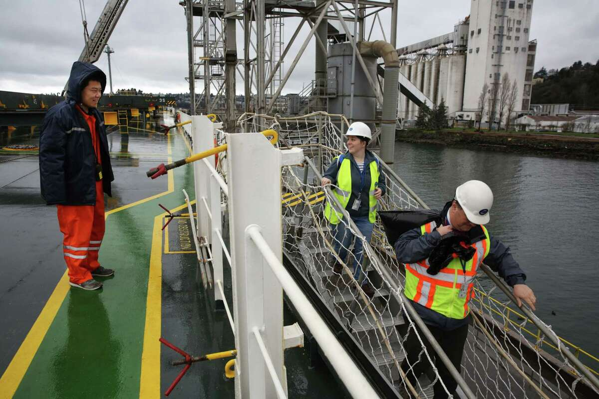 """Episcopal Bishop Greg Rickel and Assistant Port Chaplin Karen Sargent leave the Leda after bringing """"diddy bags,"""" which contain knit hats, toiletries and other gifts to the crew on Ash Wednesday, Feb. 14, 2018. Rickel, Sargent and other members of the Seafarer's Club visited ships at ports in Seattle and Tacoma to bring ashes to the crews. Many Catholic crew members are from the Philippines, Malaysia, Russia, Poland, and other eastern European countries."""
