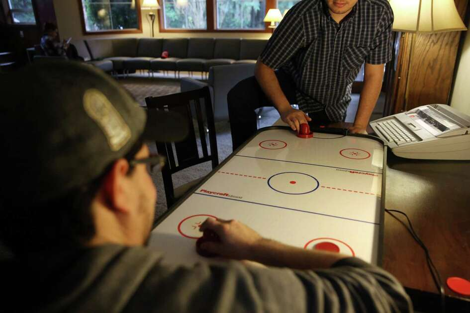 ReSTART residents play air hockey to pass the time at Heavensfield.