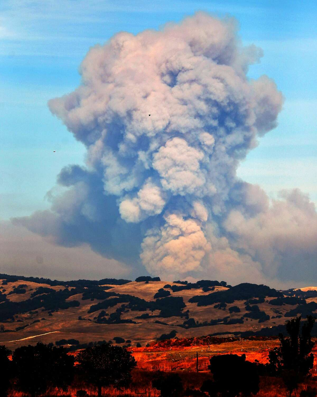 A large plume of smoke rises above the mountains between Napa and Sonoma, Calif., on Sunday, October 15, 2017.