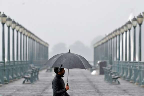 A man carrying an umbrella for protection from the rain walks along the Embarcadero in San Francisco, Calif., Sunday, November 26, 2017, as a storm dropped several inches of rain throughout the bay