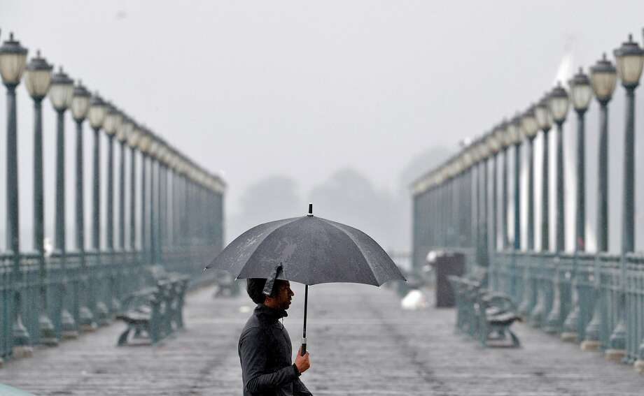 A man carrying an umbrella for protection from driving rain walks along the Embarcadero in S.F., as a fierce storm drops sev eral inches of rain in the Bay Area. A new Stanford study blames global warming for extreme weather becoming commonplace. Photo: Carlos Avila Gonzalez, The Chronicle