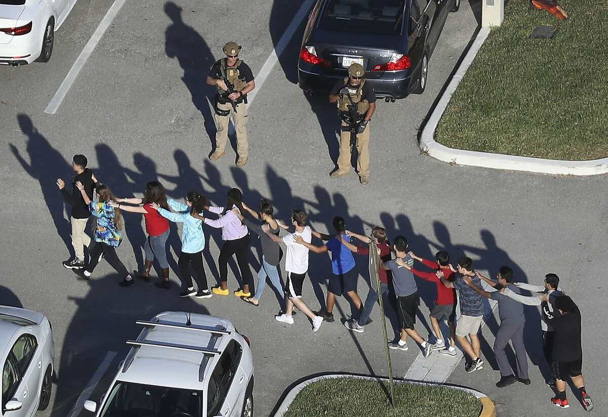 Students leave Marjory Stoneman Douglas High School after a shooting that killed 17 people on February 14, 2018 in Parkland, Florida. What would our lives in America look like without the fear of these shootings?