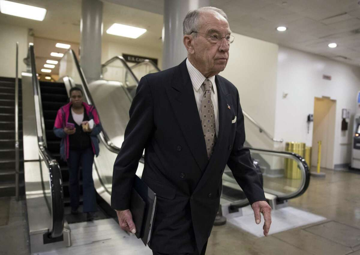 Senate Judiciary Committee Chairman Chuck Grassley, R-Iowa, walks through a basement passageway at the Capitol amid debates in the Senate on immigration, in Washington, Wednesday, Feb. 14, 2018. President Donald Trump is thanking Grassley for introducing legislation similar to the immigration framework pushed by the White House. (AP Photo/J. Scott Applewhite)